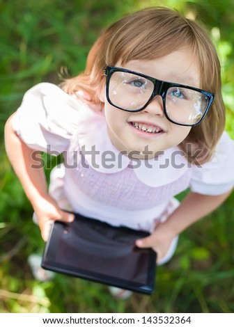 little girl in glasses with digital tablet - stock photo