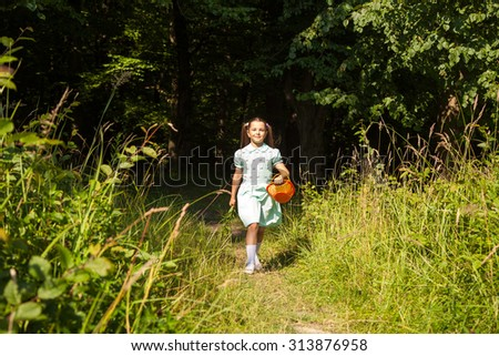little girl in green dress goes out of the forest