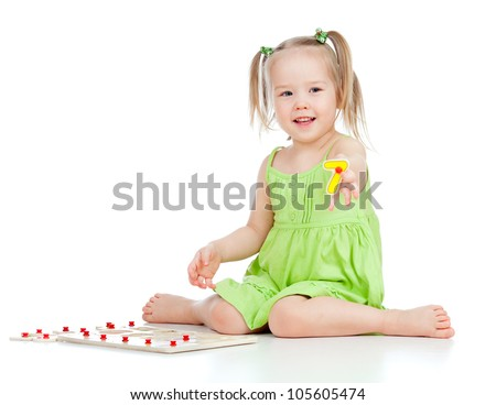 little girl in green dress playing puzzle game on floor on white background - stock photo