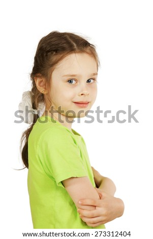 Little girl in green t-shirt stands sideways and smiling - stock photo