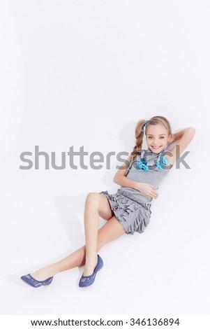 Little girl in grey dress lying on floor over white background. - stock photo