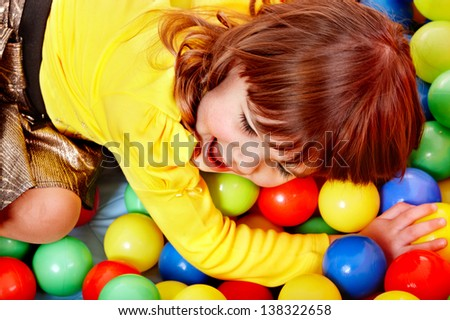 Little girl  in group colourful ball. - stock photo
