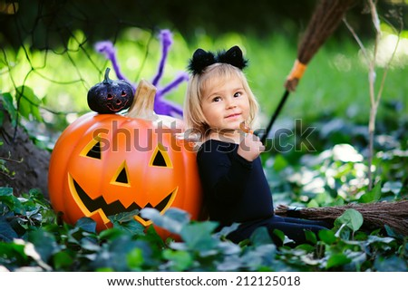 little girl in halloween costume eat sweet tricks with jack pumpkin - stock photo