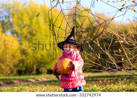 little girl in halloween costume in autumn park, kids trick or treating