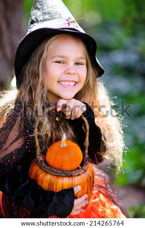 little girl in halloween costume with jack pumpkin, tick or treat - stock photo