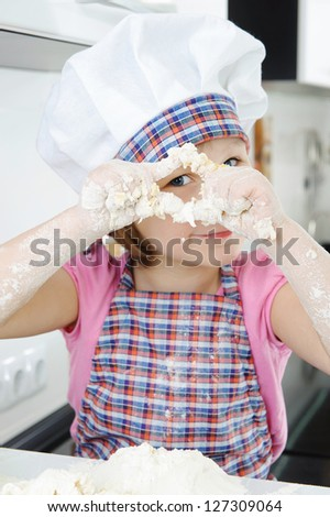 Little girl in hat and apron cooking in kitchen