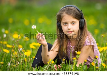 Little girl in headphones sitting in the green grass. - stock photo