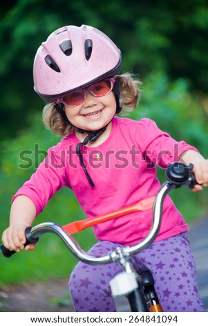 little girl in  helmet and goggles riding  bicycle - stock photo