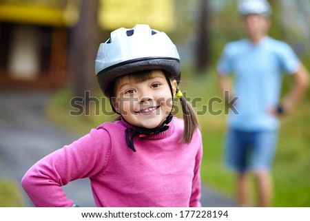 Little girl in helmet and roller skates at a park