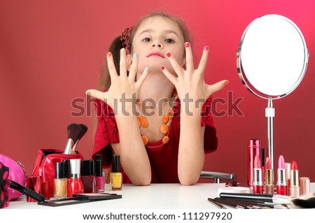little girl in her mother's dress, is trying painting her nails - stock photo