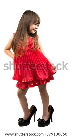 little girl in her mother's shoes on a white background - stock photo