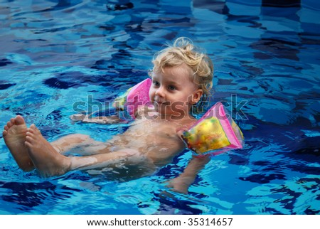 Little girl in inflatable over-sleeves floats in swimming pool - stock photo