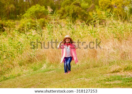 Little girl in jeans and a shirt near a river in autumn