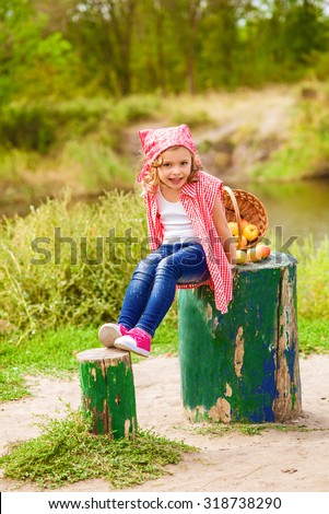 Little girl in jeans and a shirt near a river in autumn with apples