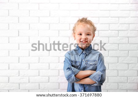 Little girl in jeans suit on a white brick wall background - stock photo
