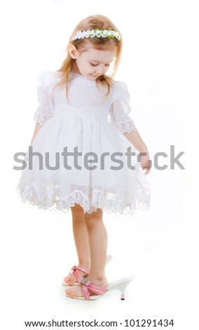 Little girl in mother's shoes  looks down on white background - stock photo
