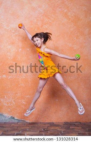 little girl in orange dress jumping beside the orange wall with orange and apple in her hands - stock photo
