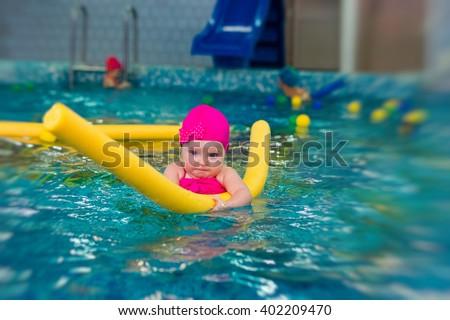 little girl in pink bikini swims in the pool - stock photo