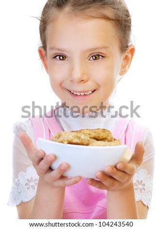 Little girl in pink dress holding plate of meat cutlets, isolated on white background.