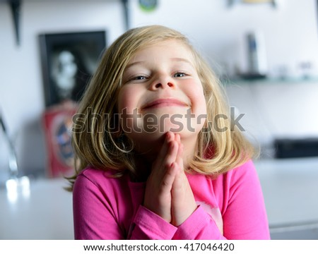 little girl in pink dress is praying - stock photo