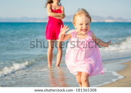 Little girl in pink dress running on the beach - stock photo