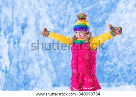 Little girl in pink jacket and colorful knitted hat catching snowflakes in winter park. Kids play outdoor in snowy forest. Children catch snow flakes. Toddler kid playing outside in snow storm. - stock photo