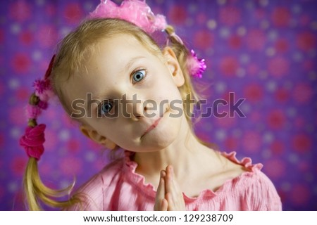 Little girl in pink making faces on a purple background