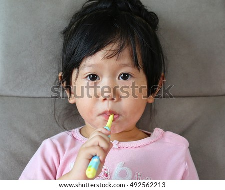 Little girl in pink on sofa brushing teeth