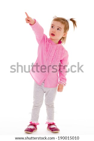 Little girl in pink shirt stands and shows a finger on a white background - stock photo