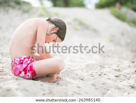 Little girl in pink shorts sitting on sand at the beach on hot summer day. Having fun during vacation. Girl playing on sand at the lake. - stock photo