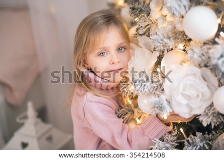 Little girl in pink sweater next to a beautiful Christmas tree, closeup portraits, the New Year celebration, holiday