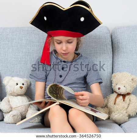 Little girl in pirate costume reading book with her plush friends. - stock photo