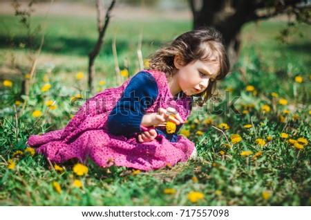 little girl in purple dress sits on a meadow . the girl has large expressive eyes