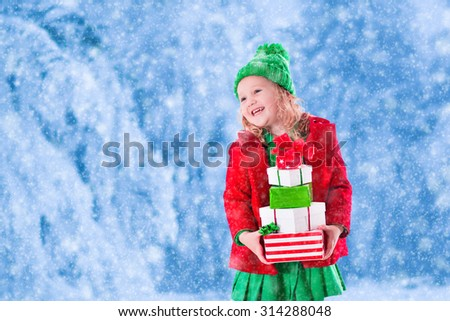 Little girl in red and green knitted hat holding Christmas present boxes in winter park on Xmas eve. Kids play outdoor in snowy winter forest. Children opening presents. Toddler kid playing with gifts - stock photo