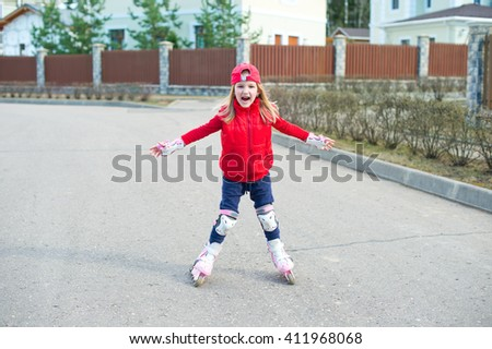 Little girl in red hat learning to skate rollers on the street of country side - stock photo