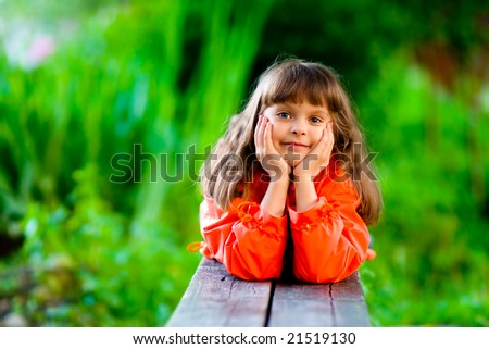 Little girl in red jacket lays on bench, having leant head on hands.
