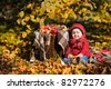 little girl in red sweater harvests of apples at golden autumn background - stock photo