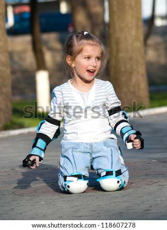 Little girl in roller skates at a park - stock photo