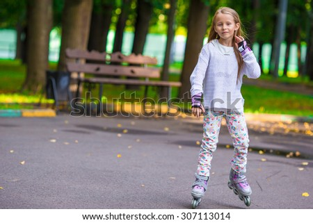 Little girl in roller skates at a park - stock photo
