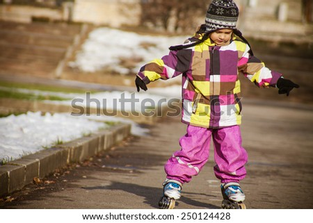 Little girl in roller skates at early spring in the park - stock photo