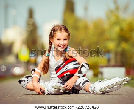 Little girl in roller skates sitting on a city street - stock photo