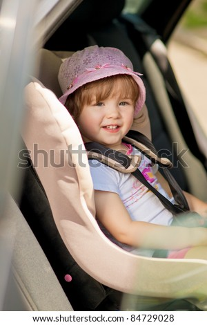 little girl in safety auto seat with smile siting