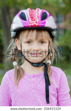 Little girl in safety helmet ready to bike or roller. Safety first concept.
