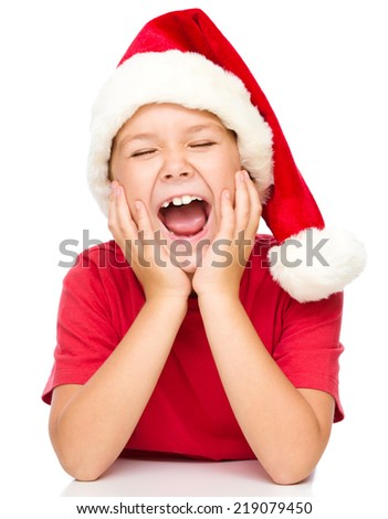 Little girl in santa hat is daydreaming supporting her head with hands and closed eyes, isolated over white