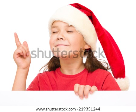 Little girl in santa hat is holding blank board and pointing up using index finger, isolated over white - stock photo