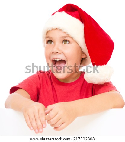 Little girl in santa hat is holding blank board and screaming, isolated over white - stock photo