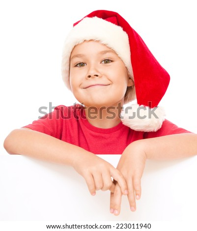 Little girl in santa hat is holding blank board and smiling, isolated over white - stock photo