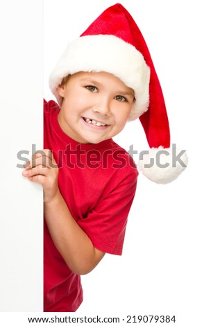 Little girl in santa hat is holding blank board, isolated over white