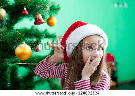 Little girl in Santa hat with Christmas decoration