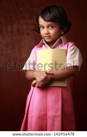 Little girl in school uniform holds a book in hand - stock photo